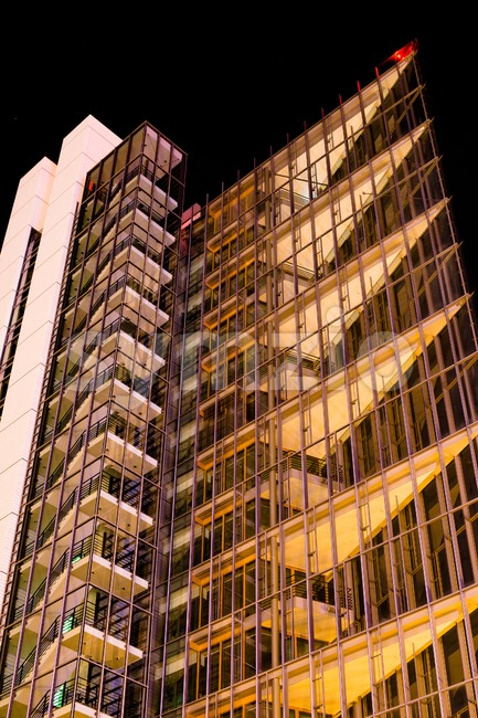 Modern multi-storey office building of glass and steel at night