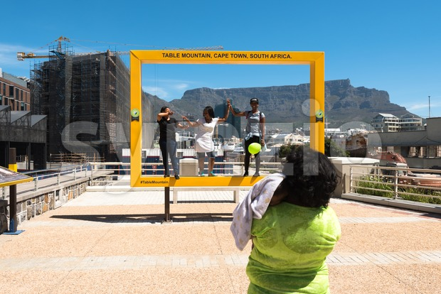 People having fun at the Table Mountain photospot at the Waterfront in Cape Town Stock Photo