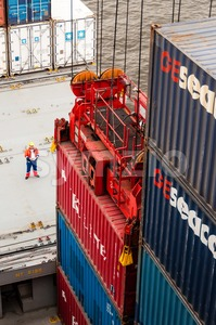 worker supervising container uploading at dock of a container ship Stock Photo