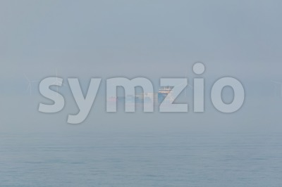Container ship passing an offshore windpark during fog Stock Photo