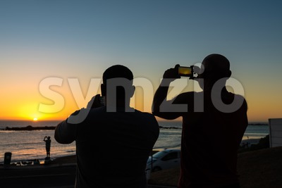 People taking photos of a sundown with their smartphones Stock Photo