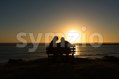 Seniors couple enjoying colorful sunset Stock Photo