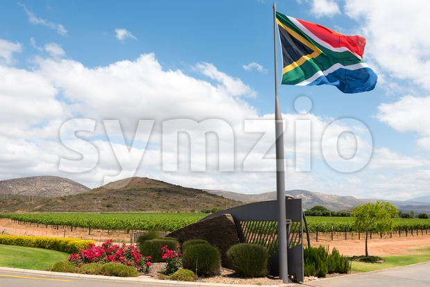 Entrance to a South African winery with flag against great blue sky