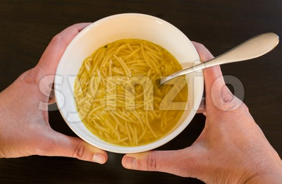 Female hands holding a bowl with European noodle soup Stock Photo