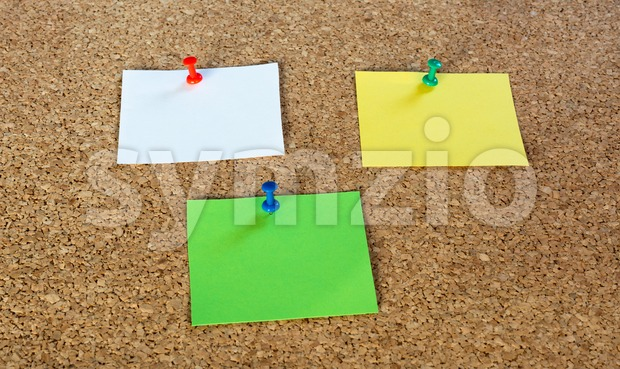 Thumbtack pins and notepaper on pinboard Stock Photo
