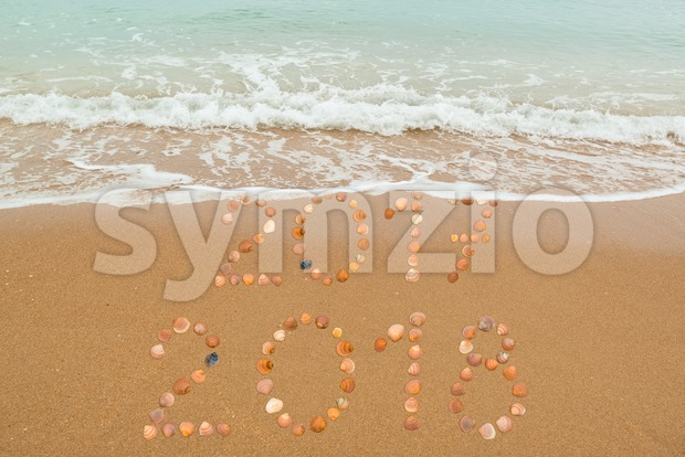 Happy New Year 2018 concept: The waves are about to cover 2017, both years placed with seashells on the beach