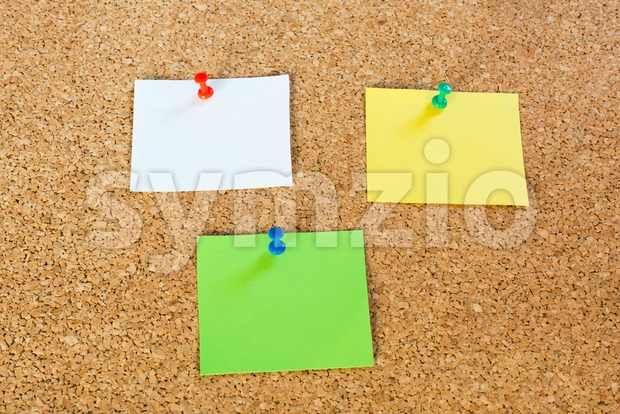 3 coloured thumbtack pins with notepapers on brown cork pinboard - copy space for your text
