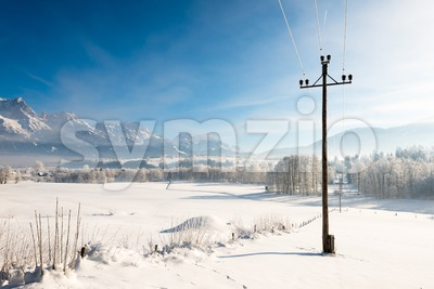 Austrian Winter Wonderland with mountains, fresh snow and haze in the sunlight Stock Photo
