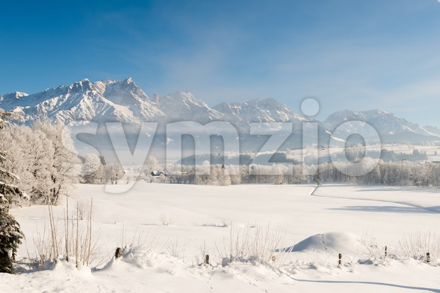Panoramic view of beautiful winter wonderland mountain scenery in the Austrian Alps with fields, forests, mountains covered by fresh snow ...
