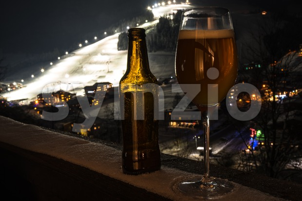 Apres Ski and craft beer concept: Glass and bottle with craft beer on a balcony looking down at a skiing ...