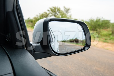 Side rear mirror of car showing elephant herd passing the street Stock Photo