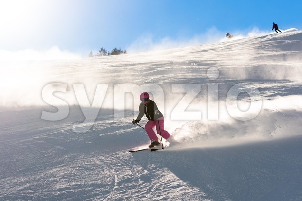Female skier in fresh powder snow and sunlight Stock Photo