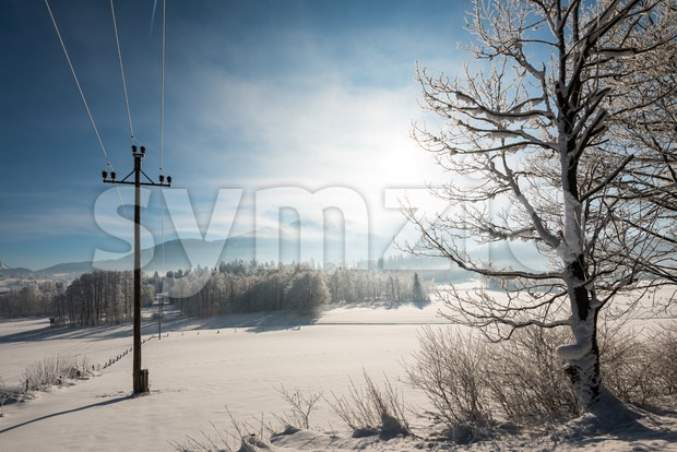Austrian Winter Wonderland with mountains, a power pole in fresh snow and haze Stock Photo