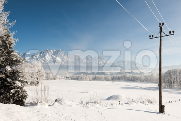 Austrian Winter Wonderland with mountains, a power pole, fresh snow and haze Stock Photo
