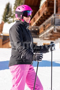 Female skier in front of skiing hut Stock Photo