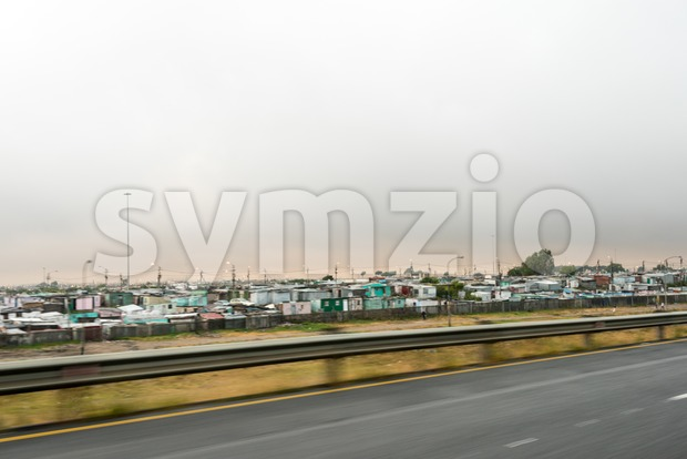 Passing the Khayelitsha township shacks near Cape Town, South Africa at dusk with first lights lit