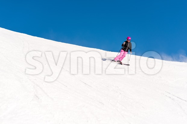 Action shot of a female sportive middle aged skier in fresh powder snow against great blue sky