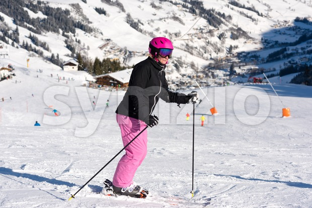Portrait of a female sportive middle aged skier in Austrian ski resort with snow cannon, skilift, skiing hut and other ...
