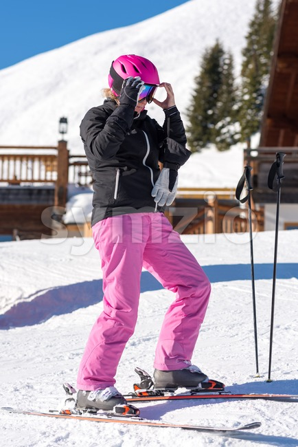 Portrait of an attractive middle aged woman getting dressed for skiing in front of a skiing hut