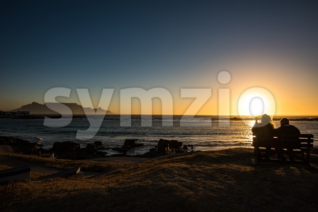 Seniors couple enjoying colorful sunset on the beach at Bloubergstrand in South Africa, facing Table Mountain. Stock Photo