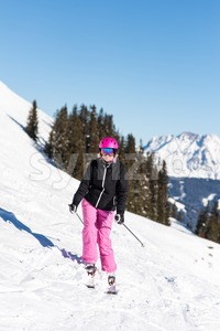 Female skier in front of trees and mountains Stock Photo