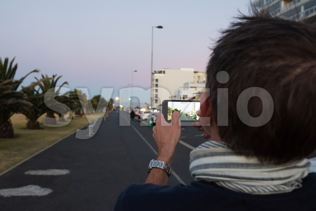 Cape Town, South Africa - November 14, 2016: A Caucasian middle aged man is filming the supermoon in Cape Town, ...