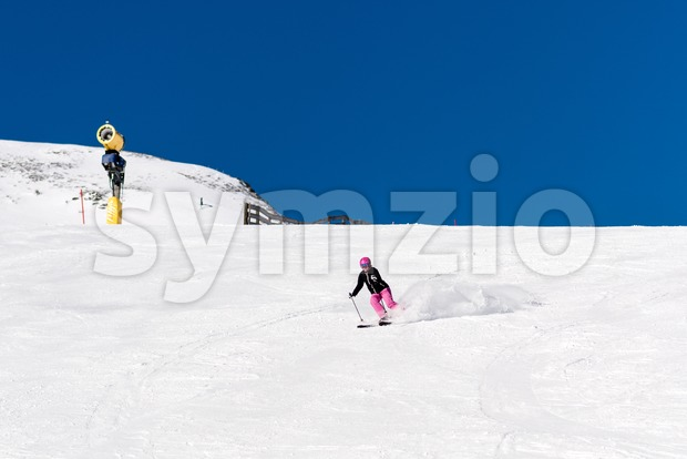 Action shot of a female sportive middle aged skier in fresh powder snow with snow cannon and blue sky in ...