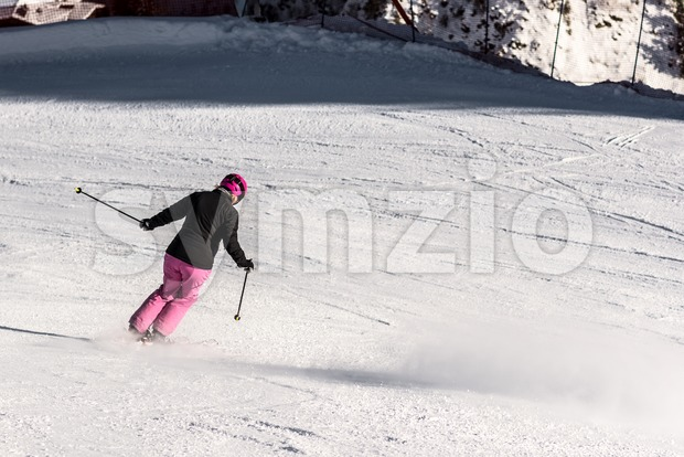 Action shot of a female sportive middle aged skier in fresh powder snow speeding downhill towards a safety net