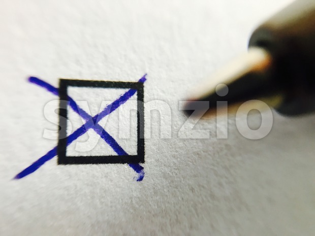 Check - ballpoint pen marking tick in check box Stock Photo