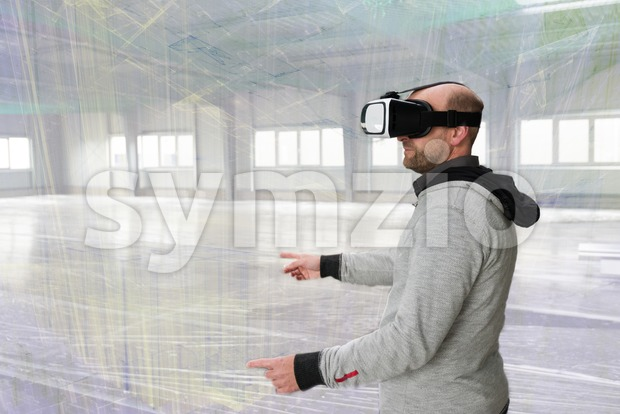 Architect with VR visor exploring industrial building environment with blueprint lines overlaying the real scenario