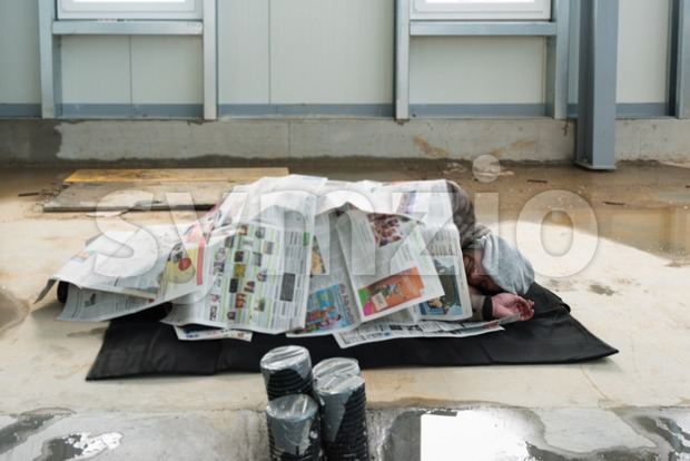 Homeless men sleeping on construction site on wet floor covered by newspapers