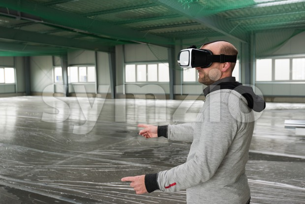 Architect with VR visor exploring industrial building environment - empty space with room for your projection visuals or text