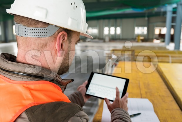 Construction supervisor checks the interior of a new warehouse being constructed with digital tablet in his hand, wearing a safety ...