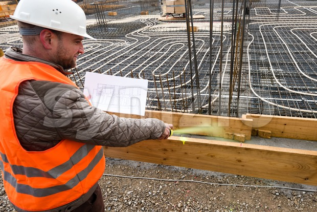 Construction supervisor oversees the construction works with a plan in his hand, marking the site with a spraycan while wearing ...