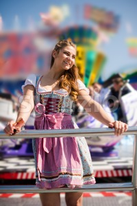 Attractive young woman at German funfair Oktoberfest with traditional dirndl dress Stock Photo