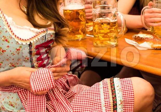 Beautiful young woman fixing her traditional Bavarian Dirndl with beer steins and friends at Munich Oktoberfest