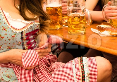 Beautiful young woman fixing her Dirndl at Munich Oktoberfest Stock Photo