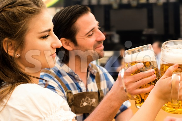 Young couple in traditional Bavarian Tracht - Dirndl and Lederhosen - in a beer tent at the Oktoberfest in Munich ...