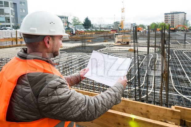 Construction supervisor oversees the construction works pointing with a plan in his hand, wearing a safety helmet and vest