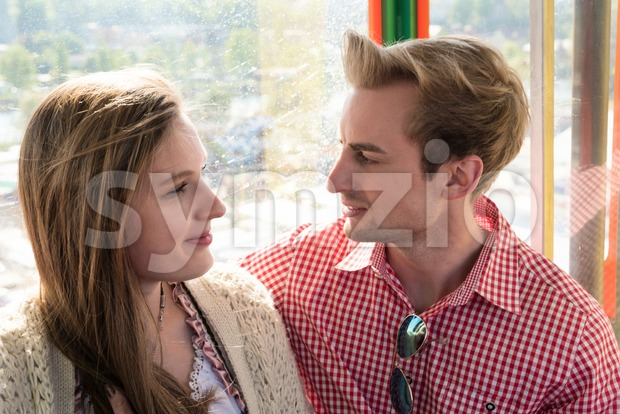 Young couple in traditional Bavarian costume in love inside a ferris wheel on Munich Oktoberfest