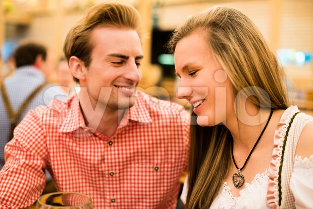 Young couple flirting in Oktoberfest beer tent Stock Photo