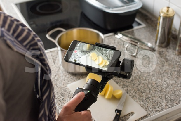 Ostfildern, Germany - May 7, 2017: A female blogger is producing a video while cooking using the DJI Osmo Mobile ...