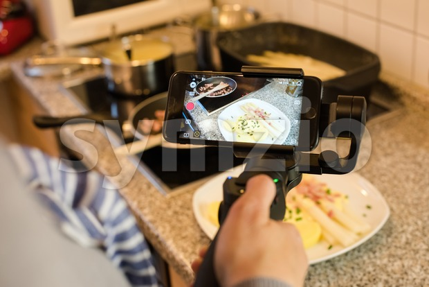 Blogger making smartphone video while preparing an asparagus dish Stock Photo