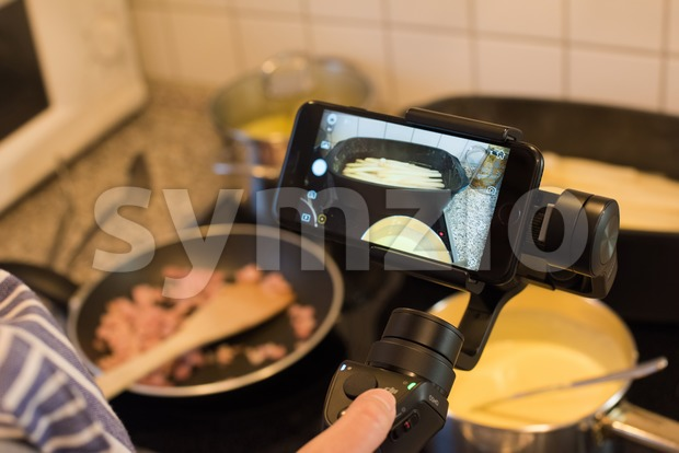 Ostfildern, Germany - May 7, 2017: A female blogger is producing a video while cooking asparagus with potatoes, ham and ...