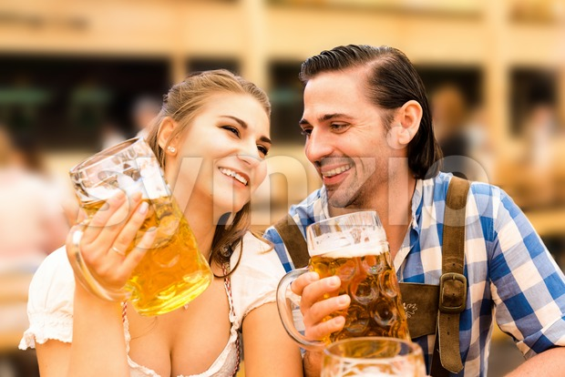 Young couple flirting in Oktoberfest beer tent while drinking beer Stock Photo