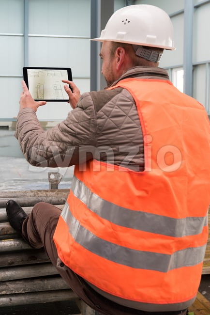 Construction supervisor checks the interior of a new warehouse being constructed with a digital tablet showing a map in his ...