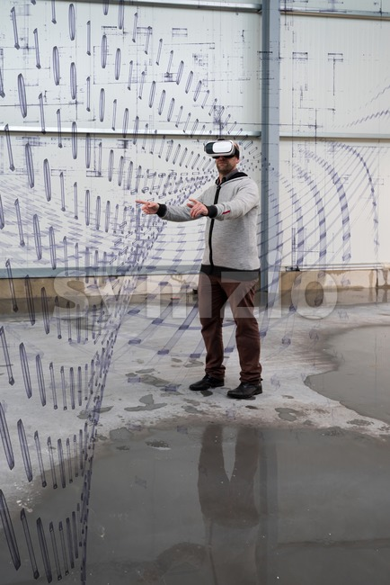 Architect with VR visor exploring industrial building environment with data objects overlaying the real scenario