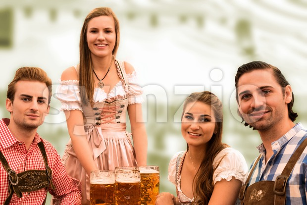 Waitress delivers beers in tent with happy visitors in a beer tent at Munich Oktoberfest against blurred greenish background