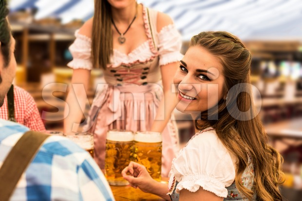 Waitress delivers beers in tent with happy visitors in a beer tent at Munich Oktoberfest Stock Photo