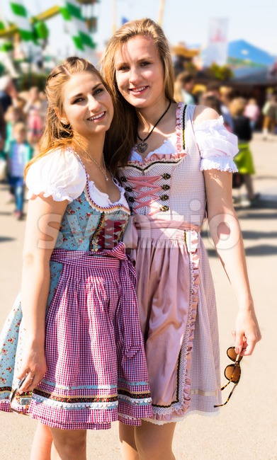 Two attractive young women at German funfair Oktoberfest with traditional dirndl dresses and merry go round in the background